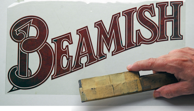 Meeks' homemade knife alongside a hand lettered logo cut in Rubylith film.